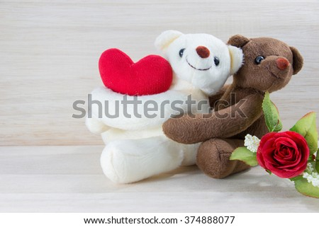Couple Teddy bear holding a heart-shaped pillow with plank wood board background.In Valentine Day.