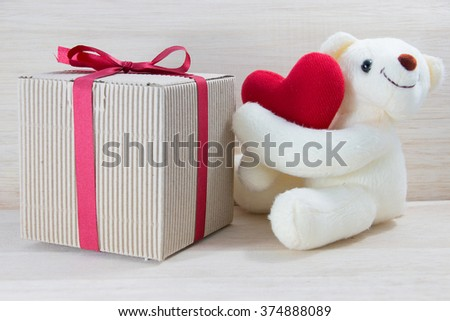Single Teddy bear holding a heart-shaped pillow with plank wood board background.In Valentine Day.
