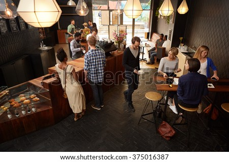 Popular modern coffee shop busy with customers and staff Royalty-Free Stock Photo #375016387