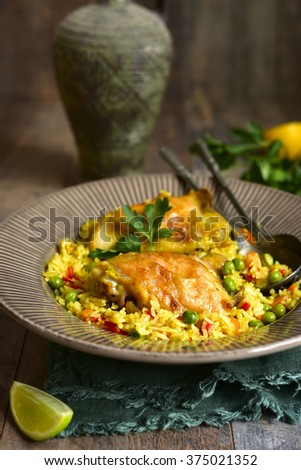 Grilled chicken with fried rice and vegetables on wooden table. #375021352