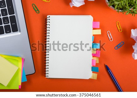 Office table desk with set of colorful supplies, white blank note pad, cup, pen, pc, crumpled paper, flower on red background. Top view and copy space for text #375046561