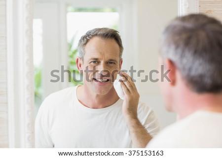 Handsome man applying shaving foam in the bathroom #375153163