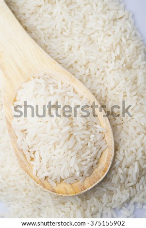 food background. brown rice in a wooden spoon. top view #375155902