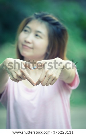 asia smiling cheerful young woman making heart sign with hands, Positive human emotion expression feeling life perception attitude body language, happy concept #375223111