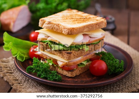 Club sandwich with cheese, cucumber, tomato, ham and eggs. #375292756