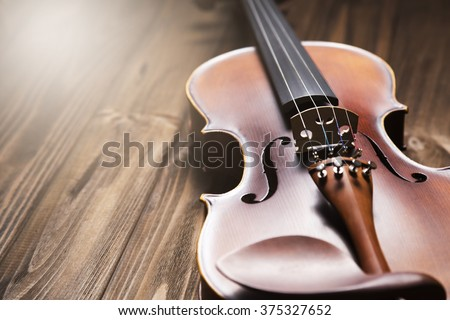 Vintage violin on the brown wooden background. Royalty-Free Stock Photo #375327652