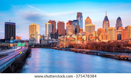 Late afternoon in Philadelphia.  The skyline glows under an orange sunset light. Schuylkill expressway traffic runs parallel to Schuylkill river.