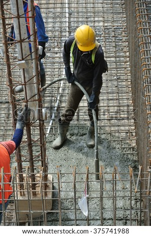 CYBERJAYA, MALAYSIA â?? AUGUST 2014: A construction worker using a concrete vibrator at a construction site in Selangor, Malaysia. Concrete vibrator is used for compacting new pouring concrete. #375741988