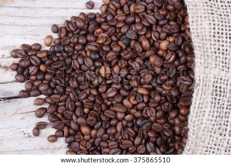 Coffee beans on the wood and burlap sack #375865510