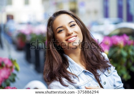 Portrait of a young woman on spring street #375886294