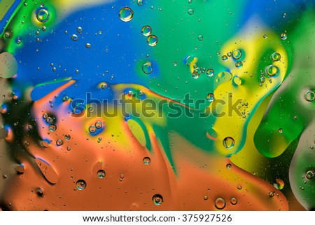 Blue, green, yellow and red abstract background made with oil drops on water #375927526