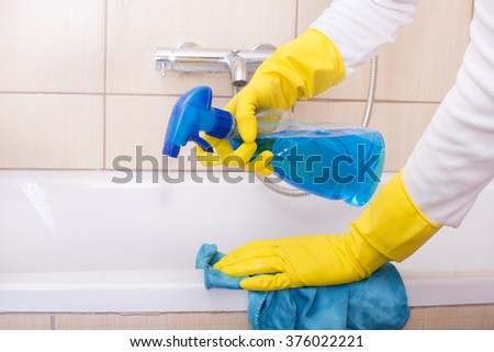Close up of female hands with rubber gloves cleaning bathtub with cloth and liquid detergent from spraying bottle #376022221