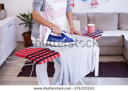 Housewife ironing a shirt in living room #376103263