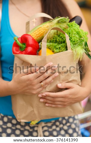 Woman with vegetables in shopping bag at street market, girl with organic food near supermarket, woman with bag of food at street market, selective focus, soft grain filter, series #376141390