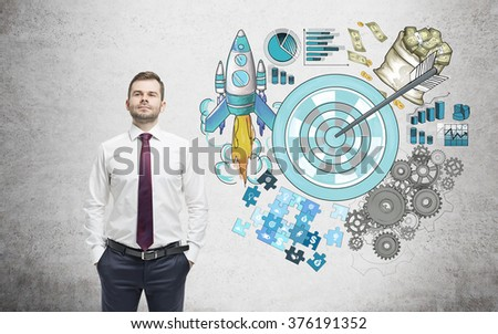 A man with hands in pockets, a picture of a target surrounded by pictures of money, rocket, charts, cogwheels and puzzles painted to the right. Concrete background. Concept of achieving a set goal.