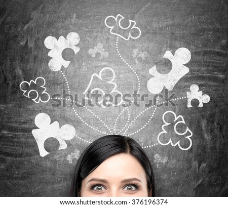 A beautiful young woman  at a blackboard with parts of a puzzle drawn on it, looking in front. Front view, only eyes seen. Concept of getting a full picture.