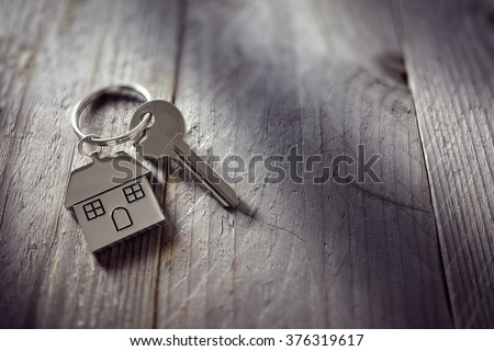 House key on a house shaped keychain resting on wooden floorboards concept for real estate, moving home or renting property Royalty-Free Stock Photo #376319617