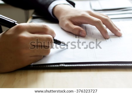 Close up Human Hand Signing on Formal Paper at the workplace #376323727