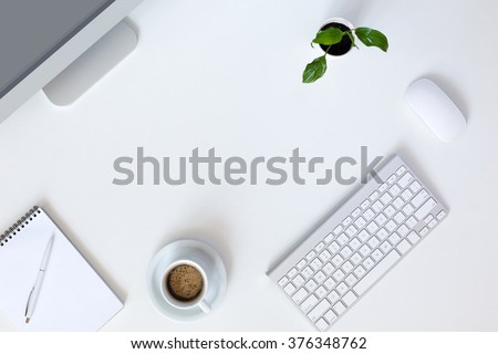 Top View of Modern Technology working Place on White Office Desk with large Desktop Computer Coffee Mug Keyboard and Mouse green Flower Notepad and Pen