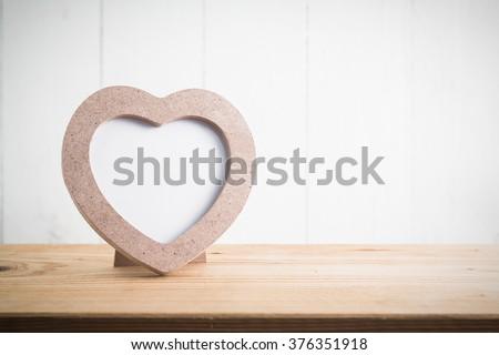 Heart shaped photo frame on wood table