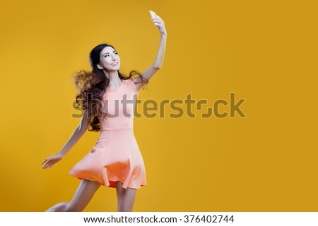 Fashion asian young  girl   taking picture of herself, selfie. Yellow background. place for your text on the right #376402744