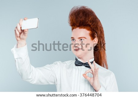 Stylish redheaded young man with bouffant on head. Boy wearing shirt with bow-tie, showing ok sign and making selfie