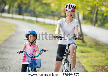 Mother and daughter are biking to the park #376494577