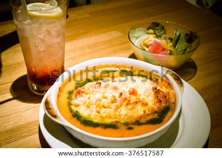 Soda drinking and Golden lasagne with meat, tomatoes, cheese sauce and pasta in alternating layers on a wooden board garnished with basil - warm and dark tone.