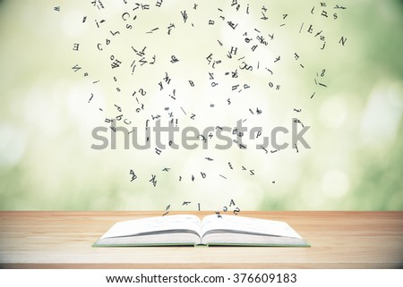 Flying letters from the opened book on wooden table #376609183