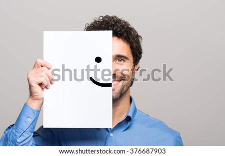 Happy man covering half his face with a smiling emoticon #376687903