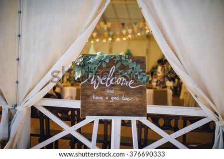 handmade wooden board with welcome sign on it decorated with eucalyptus on white stand with candlelight on background