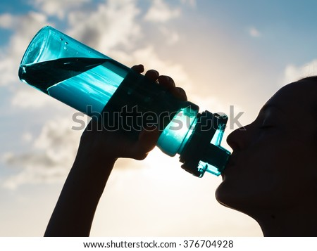 Woman drinking water.  Royalty-Free Stock Photo #376704928