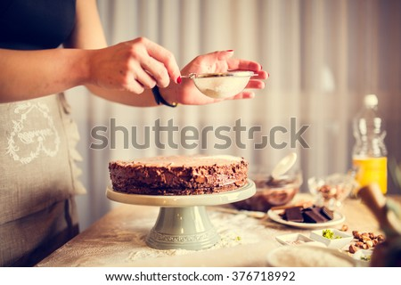 House wife wearing apron making finishing touches on birthday dessert chocolate cake.Woman making homemade cake with easy recipe,sprinkling  powdered sugar on top.Icing sugar sprinkled with colander #376718992