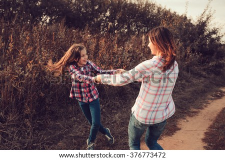 happy mother and daughter on the walk on summer field. Family spending vacation outdoor, lifestyle capture, cozy mood.