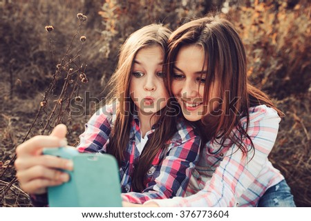 happy mother and daughter making selfie outdoor in summer. Happy family spending summer vacation together outdoor. Cozy warm mood, lifestyle capture.