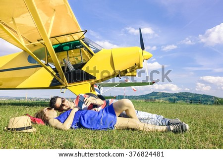 Relaxed couple of lovers having a rest during charter airplane excursion - Wanderlust concept of alternative people lifestyle traveling around the world - Love and fun watching pictures on smartphone