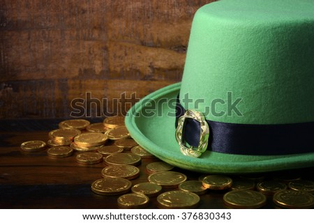 Happy St Patricks Day green leprechaun hat with gold covered chocolate coins on dark wood background.