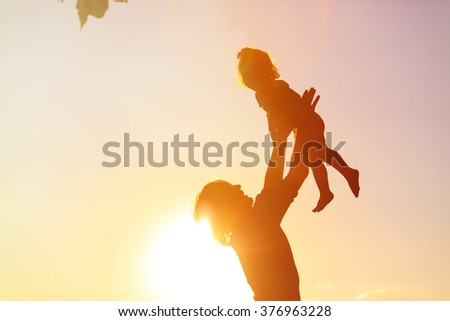 silhouettes of father and little daughter playing at sunset #376963228