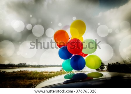 Colorful balloons on car roof,Filters image