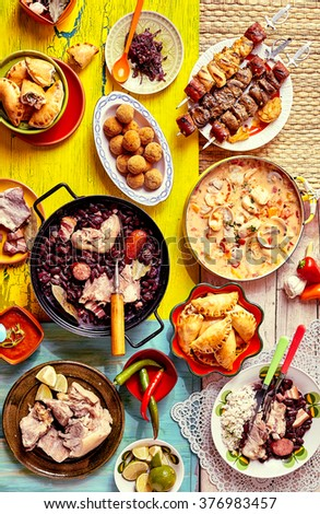 Top down view of various delicious home made Brazilian recipes displayed on colorful textures and tablecloths #376983457