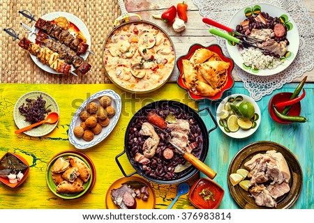 Top down view of various home made Brazilian recipes cooked and displayed on colorful textures and tablecloths Royalty-Free Stock Photo #376983814