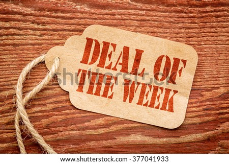 deal of the week sign a paper price tag against rustic red painted barn wood #377041933