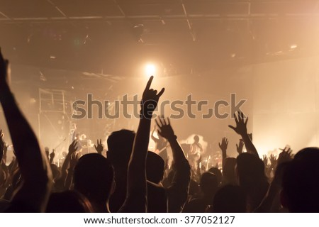 Music band crowds raising hands up in the air (very shallow depth of field)