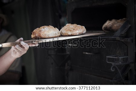 Close-up of a man baker introducing breads in a classic oven #377112013