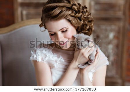 Charming and beautiful girl in white dress sitting on the couch on a background of a brick wall, smiling and holding his little gray kitten, close-up #377189830