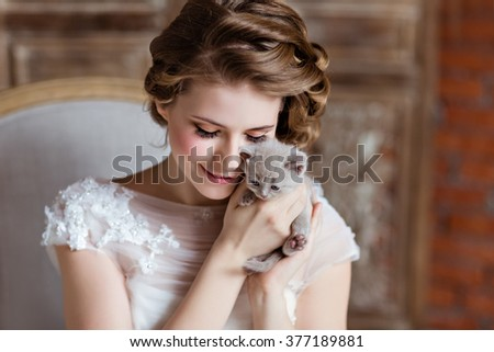 Charming and beautiful girl in white dress sitting on the couch on a background of a brick wall, smiling and holding his little kitten, close-up #377189881