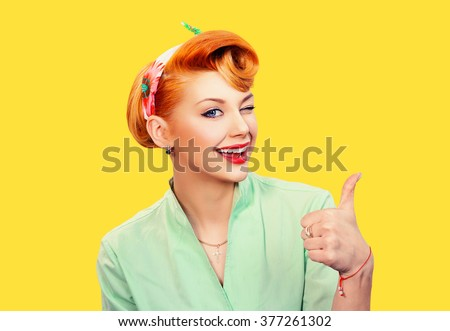 Closeup red head young woman pretty pinup girl green button shirt giving thumbs up sign gesture looking at you camera isolated yellow background retro vintage 50's style. Human emotions body language #377261302