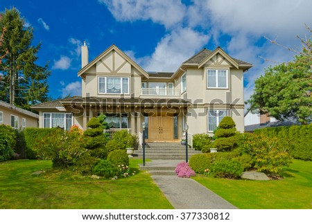 Big custom made luxury house with nicely trimmed and landscaped front yard in suburbs of Vancouver, Canada. #377330812