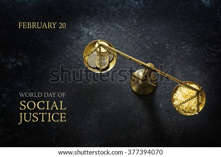 Judge balance with rice and coins on a dark slate plate, view from above, concept with text World Day of Social Justice, February 20, selected focus, narrow depth of field Royalty-Free Stock Photo #377394070