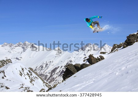 Flying snowboarder on mountains. Extreme sport. #377428945